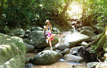 Asian hipster women take a photo of waterfall in deep forest in Thailand. Travel Concept.