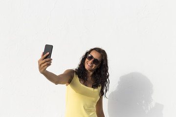 young woman taking a selfie with mobile phone over white background. sunny. summer. lifestyle