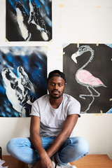 Portrait of bearded young African man with his draw picture.