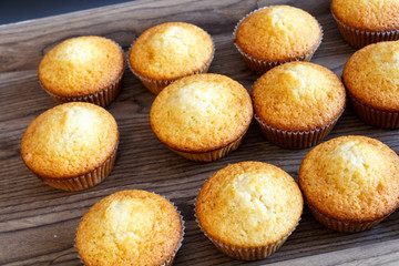 freshly baked muffins cupcakes on a natural wooden board