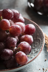 Detail of purple grapes in a bowl. Vertical