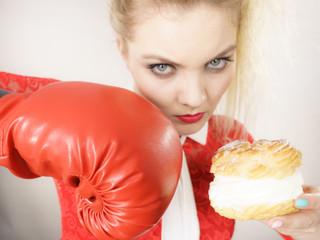 Woman fighting off bad food, boxing cream puff cake