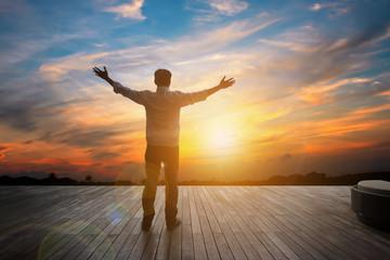 Asianman standing on wood floor in sunset sky