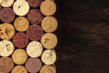 Wine corks on dark wooden texture with copyspace