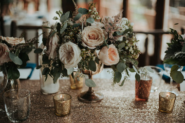 Elegant and romantic floral and shiny sequin table setting wedding decor