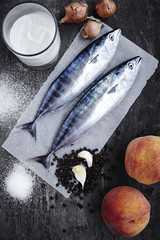 Two bonito and other ingredients on a wooden surface.