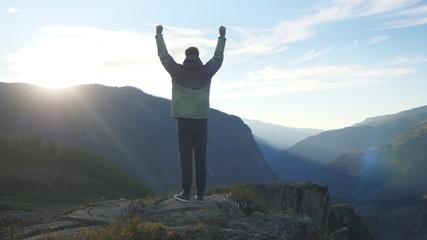 Success young man raising his hands high on top of the big mountain at beautiful golden sunset