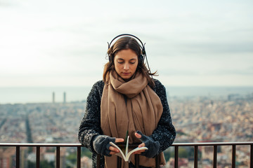 Portrait of a woman reading a book whilst listening music above city.