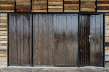 Locked wooden folding doors at bungalow in countryside. Folding doors pattern.
