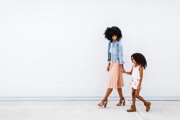 Mother and daughter walking together on sidewalk