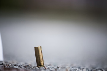 Bullet shell on the ground from the pistol. Crime scene investigation evidence of a murder. Close up of a golden bullet shell on asphalt and concrete outside. Grey color in the background