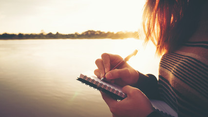 Close up hand of young woman with pen writing on notebook at riverside in the evening.