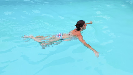 fit woman swimming in home house pool in summer