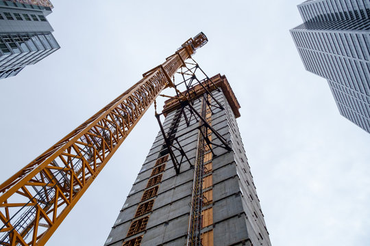 Crane attached to side of building at downtown construction site