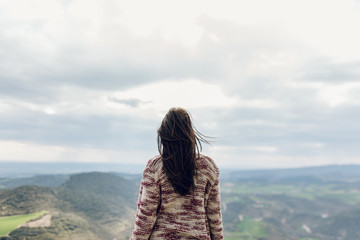 Carefree woman standing and admiring rural landscape