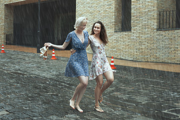 Women are walking in the rain in the city, they are smiling and happy.