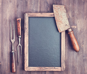 Rustic empty menu blackboard with forks and meat cleaver on wooden background with copy space