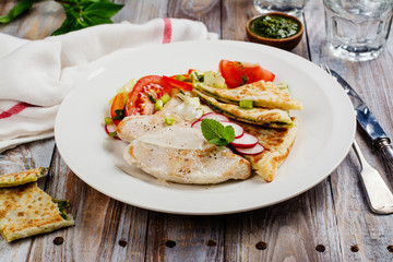 Turkey cutlets served with vegetables, pita bread with pesto and cream sauce. Copy space