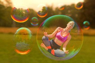 A yoga woman is hovering in a soap bubble