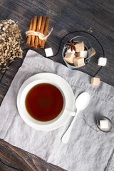 Cup of black tea on wooden table with cane and white sugar cubes, tea spoon and tea strainer. Top view.