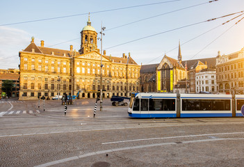 Morning view on the Dam square with Royal palace and tram in Amsterdam city during the sunny weather