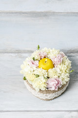 Easter floral arrangement with pink and yellow carnations.