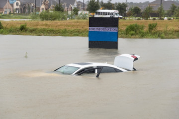 Sedan car swamped by flood water in Humble, Texas, US by Harvey Tropical Storm. Flooded car under deep on heavy high water road. Disaster Motor Vehicle Insurance Claim Themed. Severe weather concept