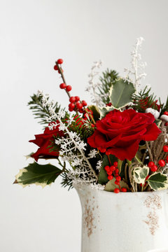 Decoration with red roses, fir, brunia and holly.