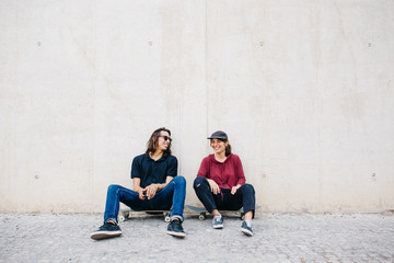 Two friends sitting on skateboards