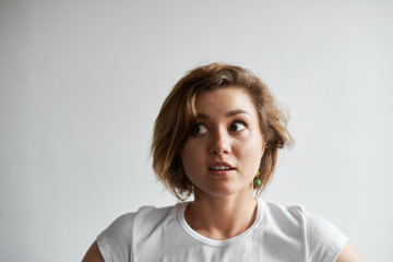 Close-up portrait of beautiful bug-eyed young Caucasian woman with short hairstyle looking sideways in shock or frustration. Human facial expressioins, emotions, reaction, feelings and attitude