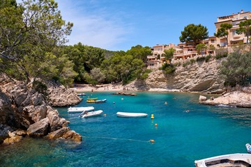 Sea bay a beautiful summer day blue clear water and granite stones. Boats above coral reef. Spain.