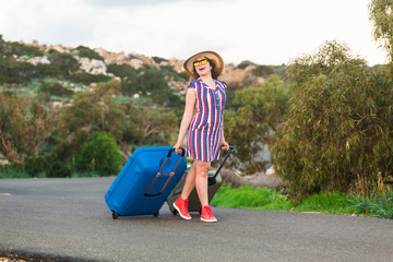 Happy cheerful traveler woman standing with suitcases on the road and smiling. Concept of travel, holidays, journey, trip