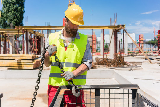 Reliable young worker checking the safety latch of a hook before lifting heavy weight with the crane on the construction site