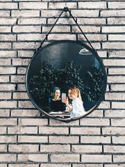 Two young women taking selfie in mirror