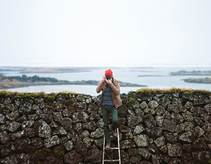 Young male photographer standing on ladder outdoors and shooting on his camera