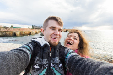 Happy traveling couple in love taking a selfie on phone at the beach on winter or autumn day. Pretty girl and her handsome boyfriend having fun, crazy emotional faces , laughing.