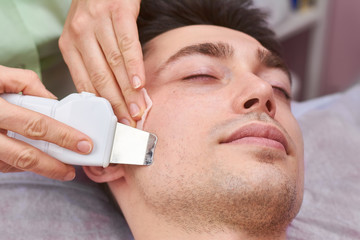 Ultrasonic face scrubber close up. Healthy young man, cosmetology.