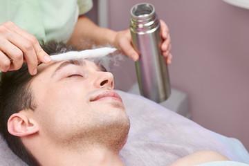 Face cryomassage, caucasian man. Skin cryotherapy close up. Liquid nitrogen use in medicine.