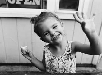 A little girl smiles with ice cream cone