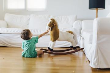 1 year old boy feeding his toy horse