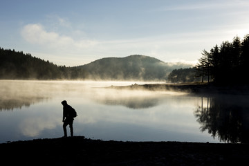 Man walking along a lake