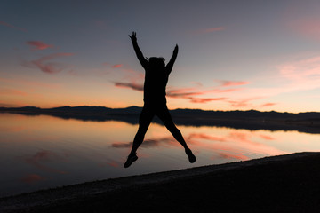 A woman jumping in the air at sunset