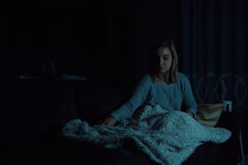 Girl fixing blanket while watching TV