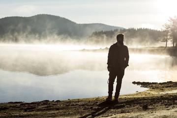Man walking along a lake