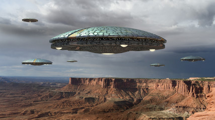 Alien spaceship fleet above the Grand Canyon, in Canyonlands, Utah, USA, for futuristic, fantasy and interstellar travel or war game backgrounds.