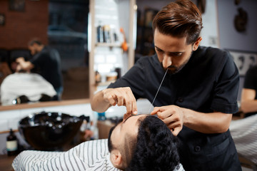 Professional hairdresser doing correction of bread with thread.
