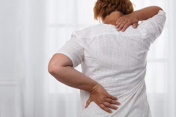 Woman suffering from back and neck pain. Chiropractic, osteopathy, Physiotherapy. Alternative medicine, pain relief concept.