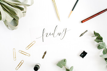 Word Friday written with calligraphy on white background with pen, brush, eucalyptus and clips. Flat lay, top view.