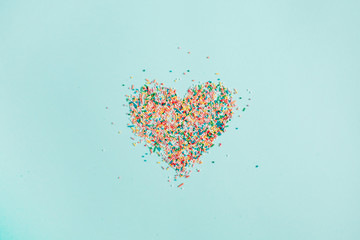 Colorful heart symbol made of confetti on blue background. Flat lay, top view.