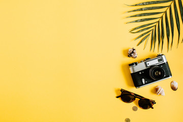 Flat lay traveler accessories on yellow background with palm leaf, camera and sunglasses. Top view travel or vacation concept. Summer background.